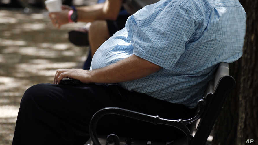 FILE - A heavyset man rests on a bench in Jackson, Miss., Sept. 4, 2014.