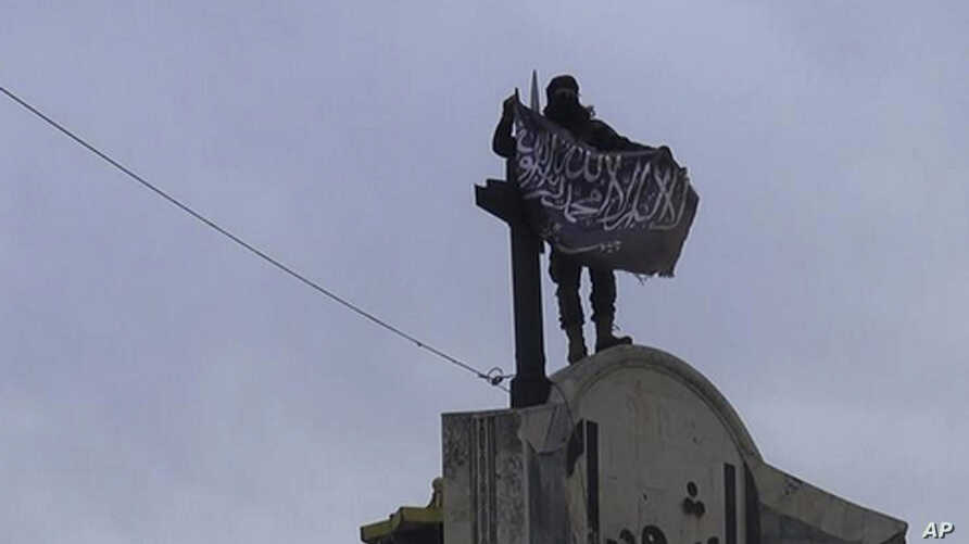 In this image posted on the Twitter page of Syria's al-Qaida-linked Nusra Front on Saturday, March 28, 2015, which is consistent with AP reporting, a fighter from Syria's al-Qaida-linked Nusra Front holds his group flag in Idlib province, north Syria
