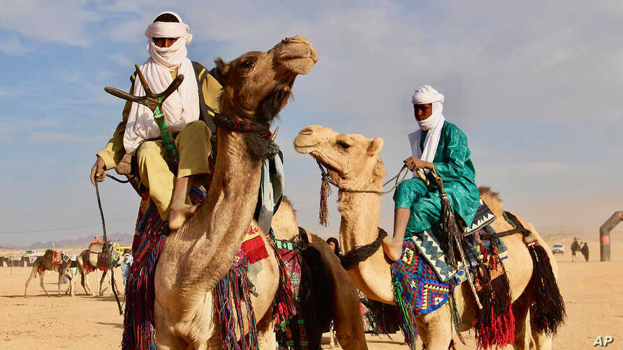 In this photo taken Feb. 18, 2018, Tuareg men ride on camels during a festival in Iferouane, Niger.
