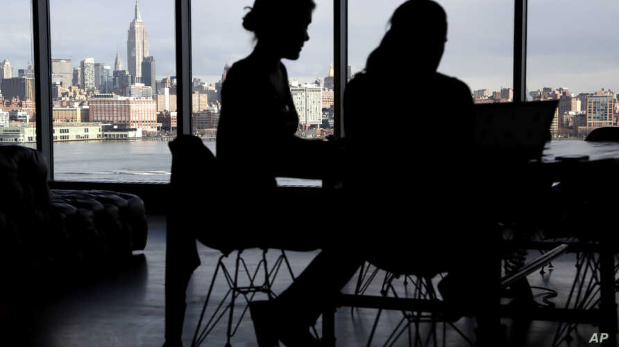 FILE - The New York City skyline is seen at a distance as two women are seen on their laptops in a building in Hoboken, New Jersey, Jan. 23, 2018.