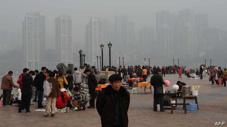 Local residents at the Chaotianmien Park in front of a newly completed social housing project in Chongqing, Feb. 3, 2013.