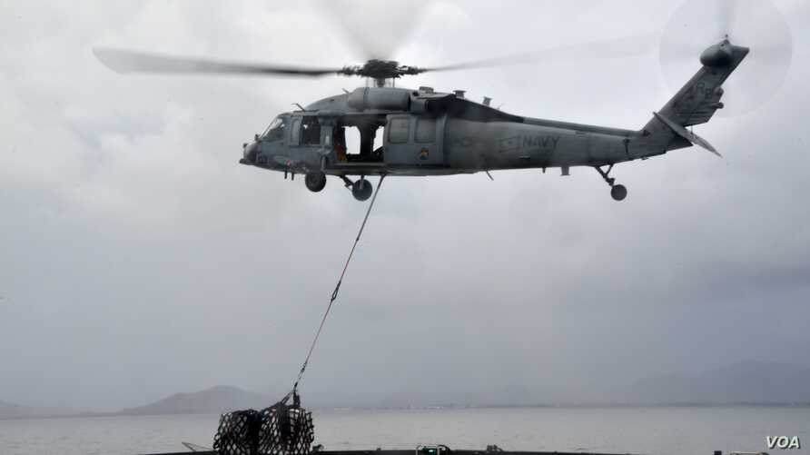 """A MH-60S helicopter, from the """"Island Knights"""" of Helicopter Sea Combat Squadron (HSC) 25, from the Military Sealift Command dry cargo and ammunition ship USNS Charles Drew (T AKE 10), transports a pallet of water en route to the Republic of the ..."""