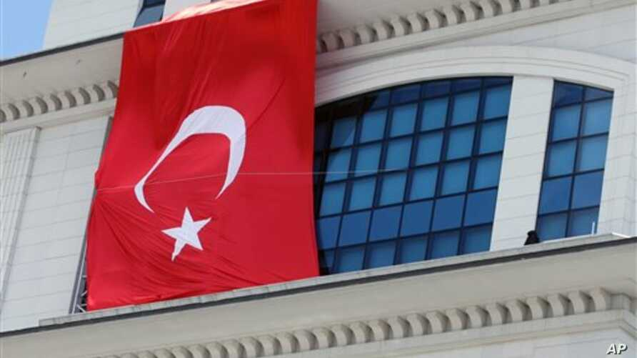 A Turkish flag is hung from the headquarters of Turkish Prime Minister Recep Tayyip Erdogan's ruling party, apparently to conceal the damage after assailants fired a rocket on the building, in Ankara, Turkey, March 20, 2013.