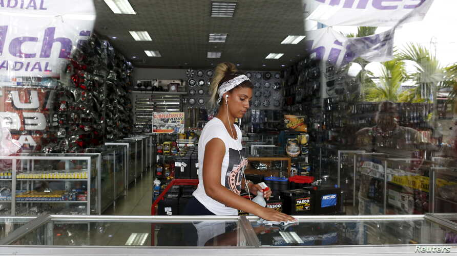 """Cuban migrant Halena Leiva, 31, who ran out of money, works as a cleaning lady in an auto store in Paso Canoas, Panama, March 22, 2016. """"I am a qualified  IT engineer. If I hadn't left Cuba I would have ended up in prison as I love freedom and having"""