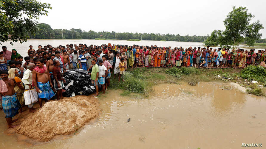 People wait for relief supplies on a flooded island in Howrah district, West Bengal, India, July 28, 2017.