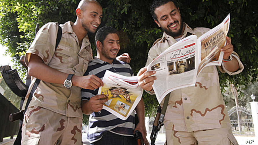 Anti-Gadhafi fighters read a newspaper where a wanted poster for Moammar Gadhafi was published in Tripoli September 1, 2011.