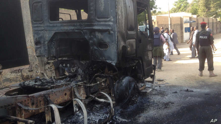 In this photo taken with an iPad policemen stand guard at a burned out truck following an attack by Boko Haram Islamists near an air force base in Maiduguri, Nigeria, Dec, 2. 2013.