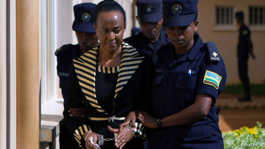 Adeline Rwigara, mother of Diane Shima Rwigara, a prominent critic of Rwanda's President Paul Kagame, is escorted by police officers into a courtroom in Kigali, Rwanda, Oct. 11, 2017.