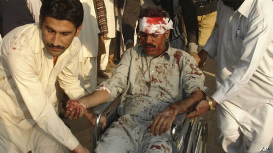 A man injured by a bombing in Dera Ghazi Khan is helped by local residents, 15 Dec 2009