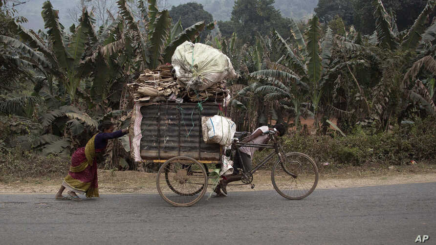 An impoverished Indian family transports recyclable material on a cart on the outskirts of Gauhati, India, Wednesday, Feb. 1, 2017.