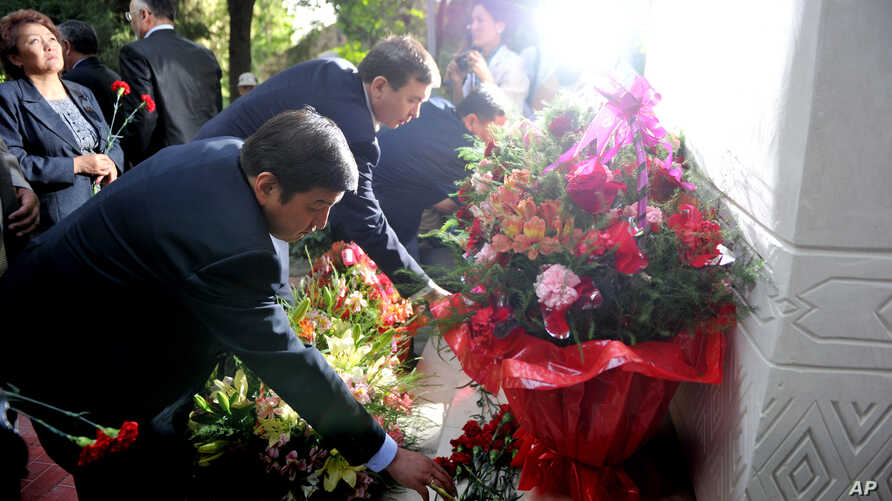 FILE - People lay flower tributes during ceremony marking first anniversary of violence between ethnic Kyrgyz and minority Uzbeks in the southern city of Osh, Kyrgyzstan, June 10, 2011.