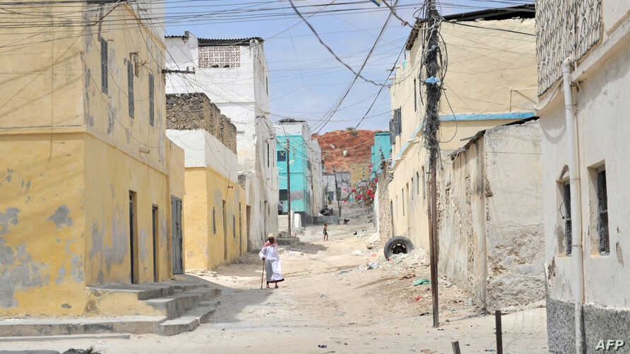 FILE - A handout photo taken on February 12, 2016 and released by AMISOM shows an elderly man walking through a street alley in the Somali port city of Merca, Lower Shabelle Region, Somalia.