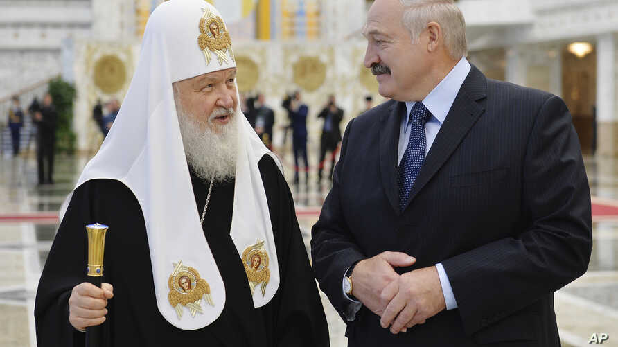 Belarusian President Alexander Lukashenko, right, and Russian Orthodox Church Patriarch Kirill walk during their meeting in Minsk, Belarus, Oct. 15, 2018.