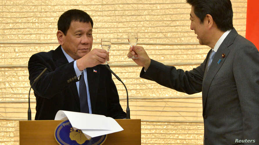 FILE - Philippines President Rodrigo Duterte (L) toasts with Japan Prime Minister Shinzo Abe during a banquet at Abe's official residence in Tokyo, Oct. 26, 2016.