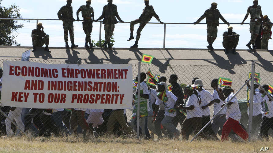 Zimbabwean soldiers lookon as Zanu pf youths march for President Robert Mugabe  at a rally in Bulawayo, June 20, 2008. Mugabe who faces Morgan Tsvangirai in a run off election set for June 27 warned Zimbabweans not to vote for the opposition as this