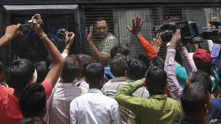 An Indian man convicted for the 2002 Gujarat riots is taken back to jail after the court announced the lengths of the sentences in Ahmadabad, India on June 17, 2016.