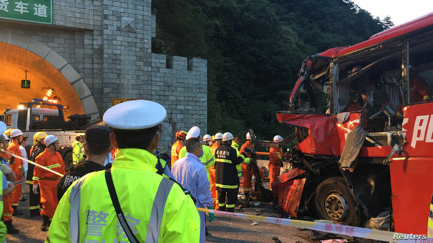 Police and firefighters work near the wreckage of a coach after it crashed into the wall of a tunnel along the Xi'an-Hanzhong expressway in Ankang, Shaanxi province, China, Aug. 11, 2017.