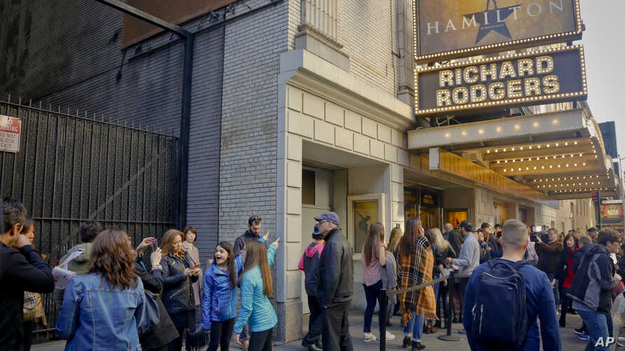 """People line up to see the Broadway play """"Hamilton,"""" Nov. 19, 2016, in New York. President-elect Donald Trump demanded an apology from the cast of the hit musical a day after an actor lectured Vice President-elect Mike Pence about equality."""