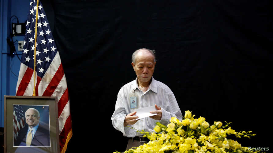 Vietnamese veteran Pham Minh Chuc, 81, pays respect after he wrote in a condolence book near a portrait of U.S. Senator John McCain (R-AZ) about his death at the U.S. embassy in Hanoi, Vietnam, Aug. 27, 2018.