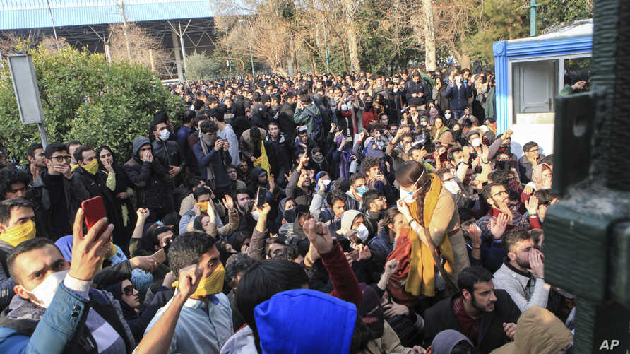 FILE - In this Saturday, Dec. 30, 2017 file photo taken by an individual not employed by the Associated Press and obtained by the AP outside Iran, university students attend a protest inside Tehran University while anti-riot Iranian police prevent th