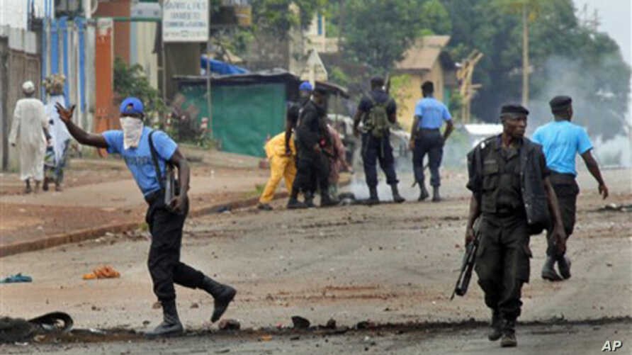 Guinean police carrying automatic weapons clear the mostly Peul suburb of Bambeto in Conakry, Guinea, 16 Nov.2010, as groups of UFDG youth set up barricades. A de-facto curfew is in effect in the area, residents staying inside, one day after it was a