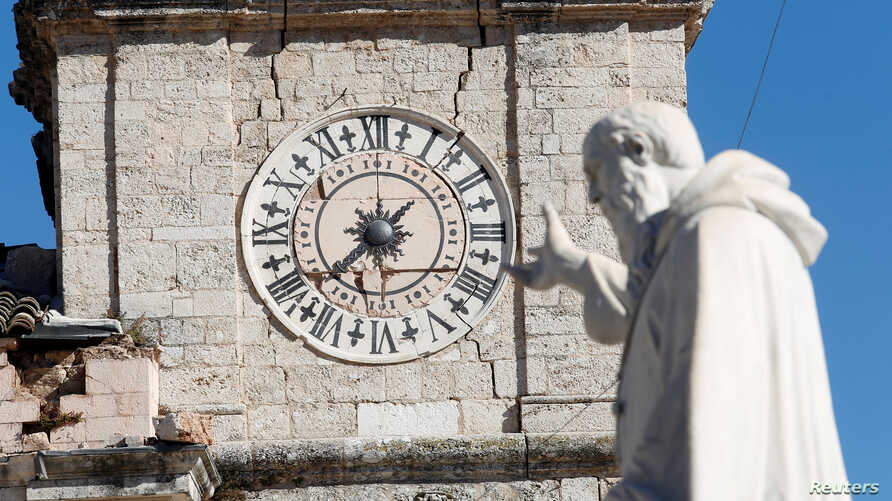 A statue of St. Benedict gestures toward the clock of the damaged town hall tower in the ancient town of Norcia, Italy, Oct. 31, 2016.