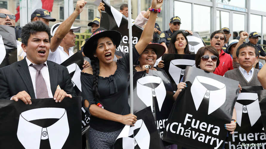 """People hold placards reading """"Chavarry out"""" referring to Peru Attorney General Pedro Chavarry, during a protest outside the Attorney General's Office in Lima, Peru, Jan. 8, 2019."""