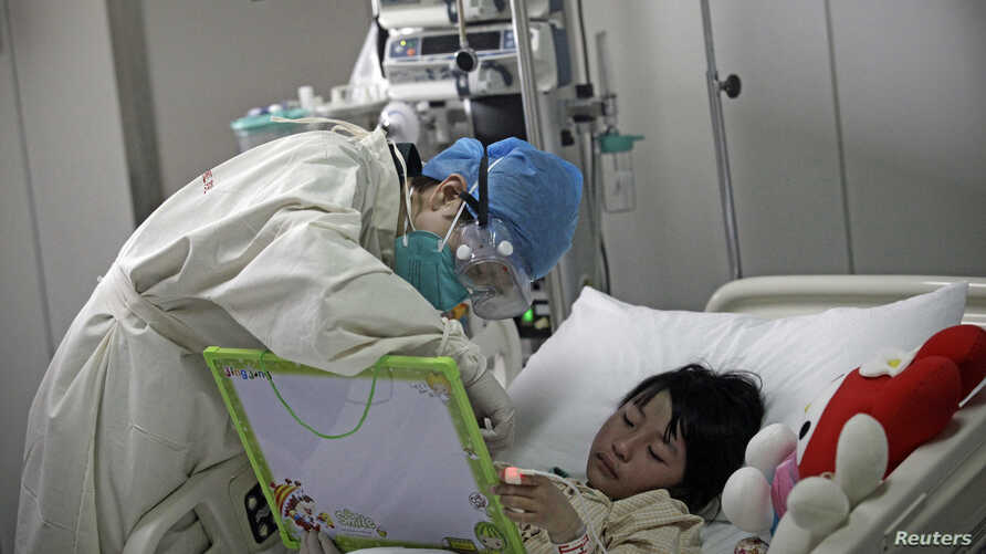 A girl infected with the new H7N9 bird flu strain draws a picture with a nurse at Ditan Hospital in Beijing, April 2013.