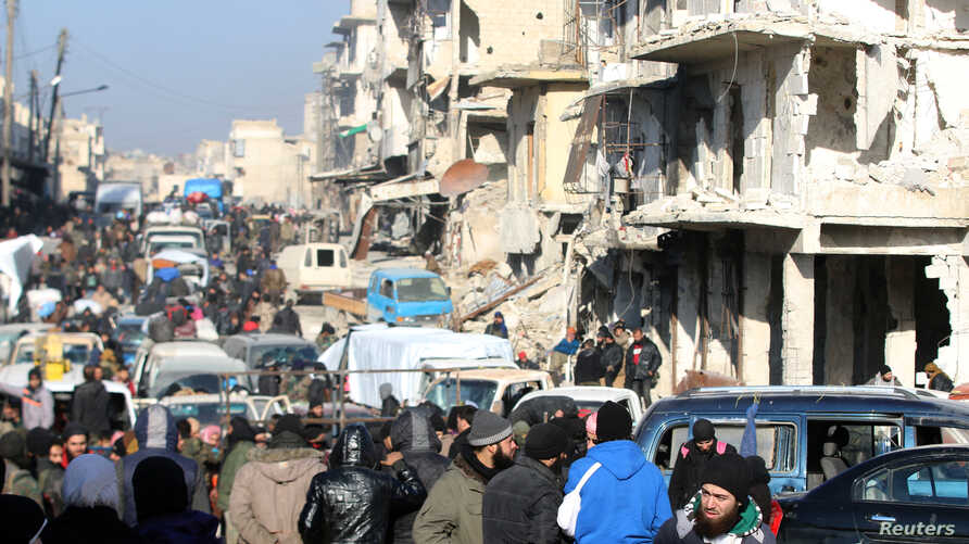 FILE - Rebel fighters and civilians wait near damaged buildings to be evacuated from a rebel-held sector of eastern Aleppo, Dec. 18, 2016.