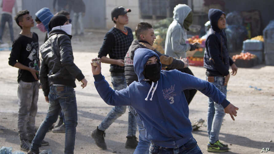 A Palestinian protester throws stones during clashes with the Israeli military in the West Bank village of Kabatiya, near Jenin, Feb. 5, 2016.