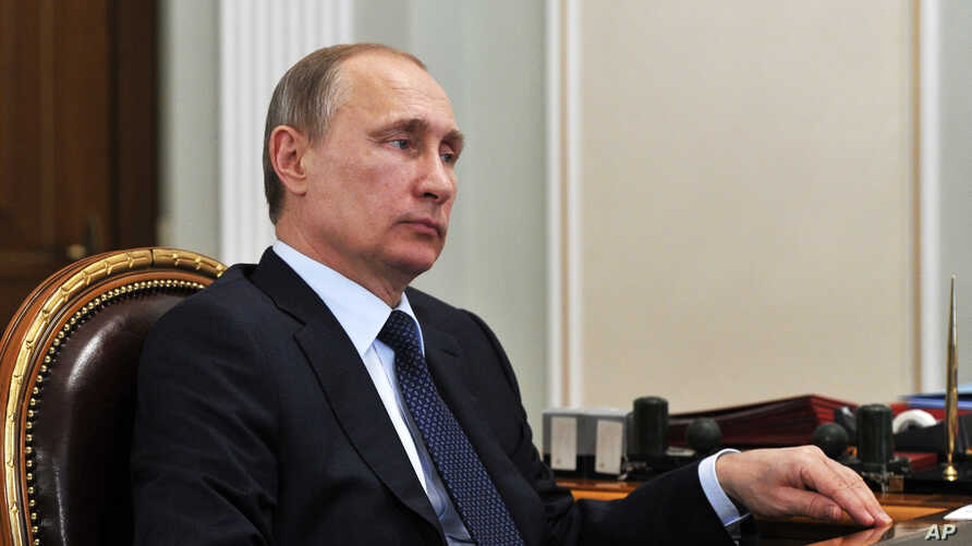 Russian President Vladimir Putin listens during a meeting in the Novo Ogaryovo residence, outside Moscow on Monday, April 13, 2015.