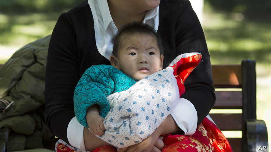 FILE - A child is wrapped up against the cold at a park in Beijing, China.