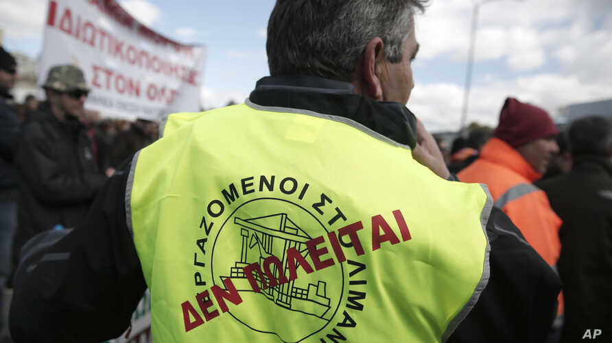 """FILE - A dock worker with a """"Not for sale"""" sign on his vest takes part in a protest against government plans to further privatize the harbor of Piraeus, Greece."""