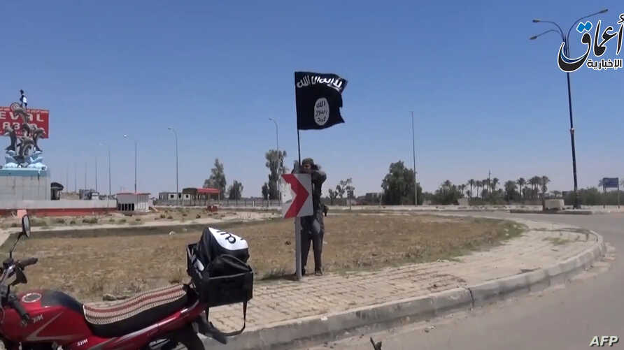An image taken from a video uploaded on May 18, 2015 by Aamaq News Agency, a Youtube channel which posts videos from areas under the Islamic State (IS) group's control, allegedly shows an IS fighter hanging a flag of the group in a street of Ramadi,