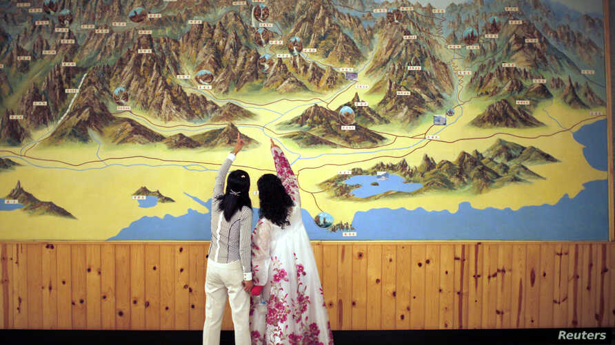 FILE - People point to a map on a wall in Mount Kumgang resort in Kumgang, Sept. 1, 2011.