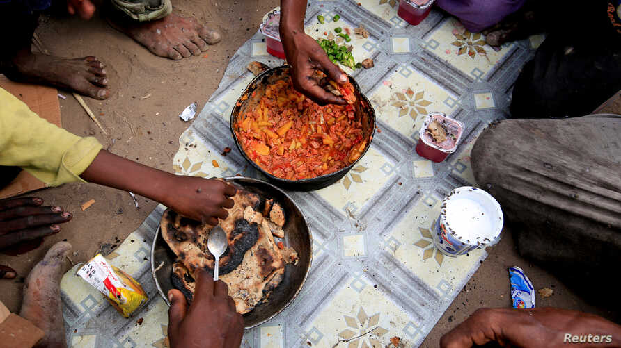 Members of the Ruzaiq family eat a meal outside their hut, next to a garbage dump where they collect recyclables and food near the Red Sea port city of Hodeidah, Yemen, Jan. 9, 2018.