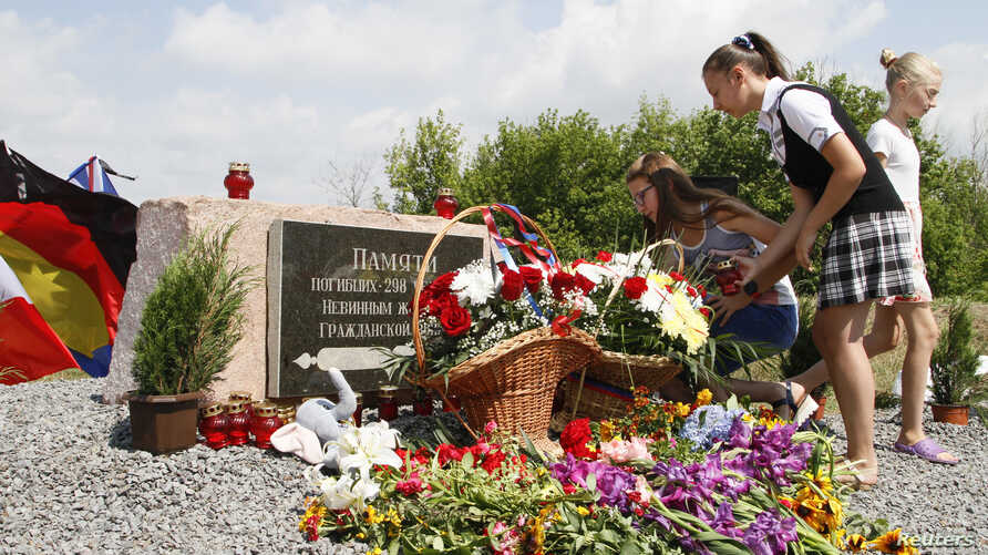 People gather near a monument for the victims of the Malaysia Airlines flight MH17 plane crash to mark the fourth anniversary of the accident near the village of Hrabove (Grabovo) in Donetsk Region, Ukraine July 17, 2018.