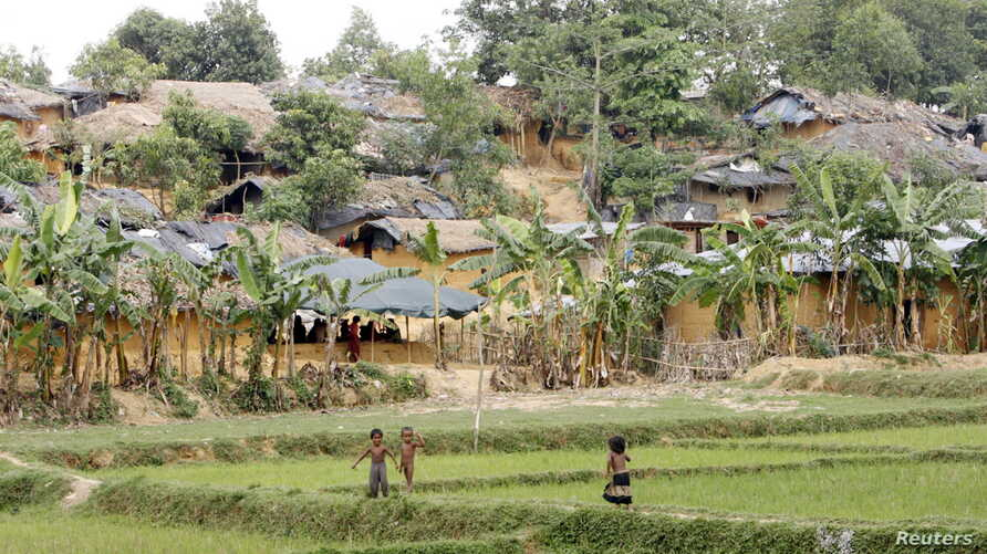 Children stand near camps housing Rohingya refugees on hills in Kutupalong, Bangladesh, May 31, 2015.