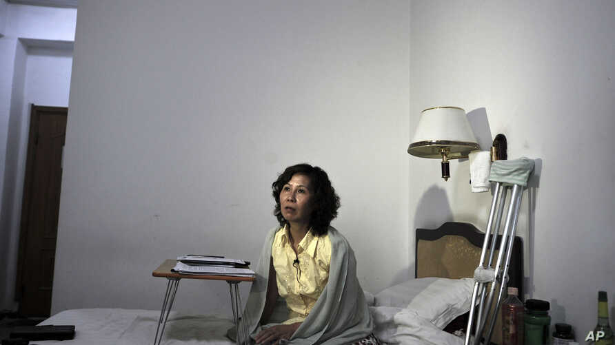 In this photo taken on June 30, 2010, Ni Yulan sits on the bed in a hotel in Beijing.