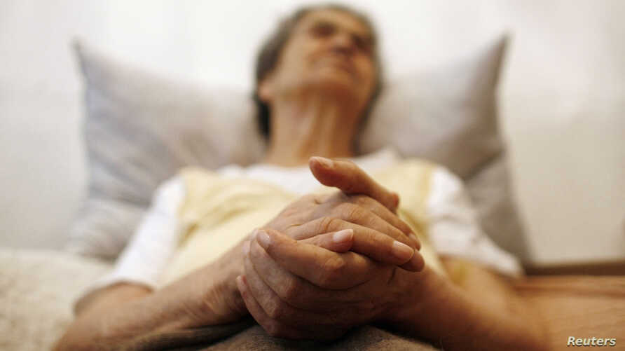 FILE - Alzheimer's disease patient Isidora Tomaz, 82, sits in an armchair in her house in Lisbon, Portugal, Sept.15, 2009.