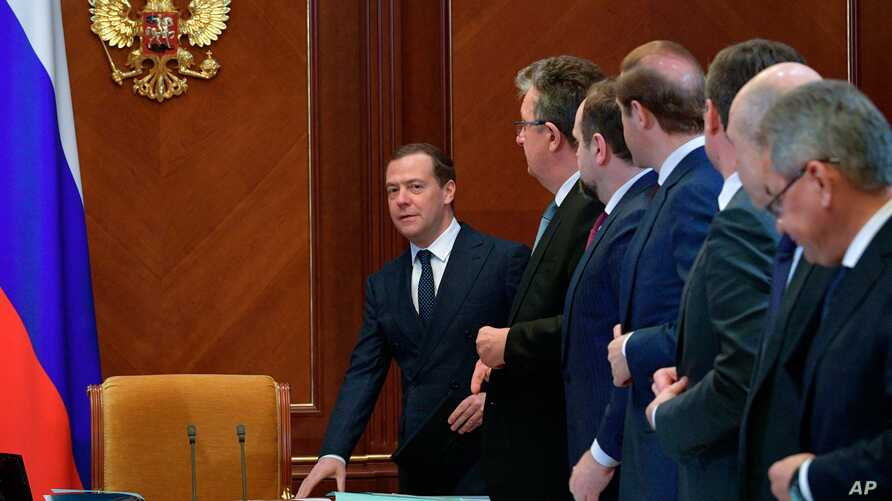 FILE - Russian Prime Minister Dmitry Medvedev, left, arrives to lead a cabinet meeting in the Gorky residence outside Moscow, Russia, April 28, 2018.
