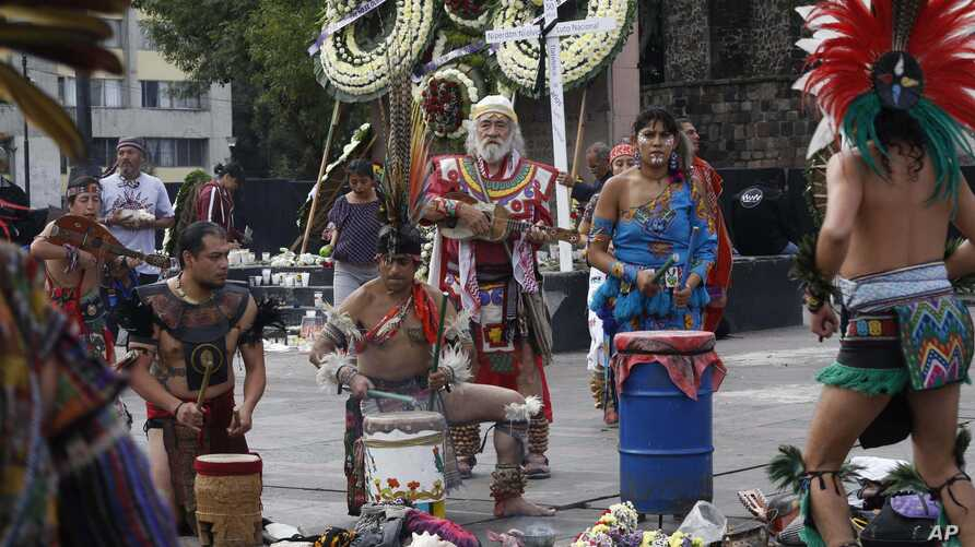 Aztec drummers and dancers perform in Tlatelolco plaza where wreaths have been laid in commemoration of the 1968 massacre of student protesters by army troops 50 years ago, in Mexico City, Tuesday, Oct. 2, 2018. Students and surviving leaders of the