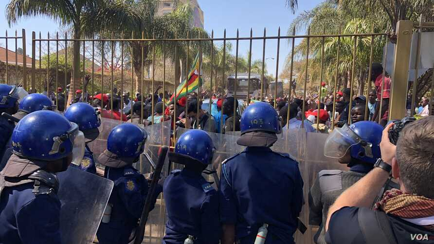 Human rights groups accuse President Emmerson Mnangagwa's government of high handiness and not allowing opposition and dissent. Here police block opposition members, Aug. 1, 2018, in Harare from protesting against delaying in announcement of July 30