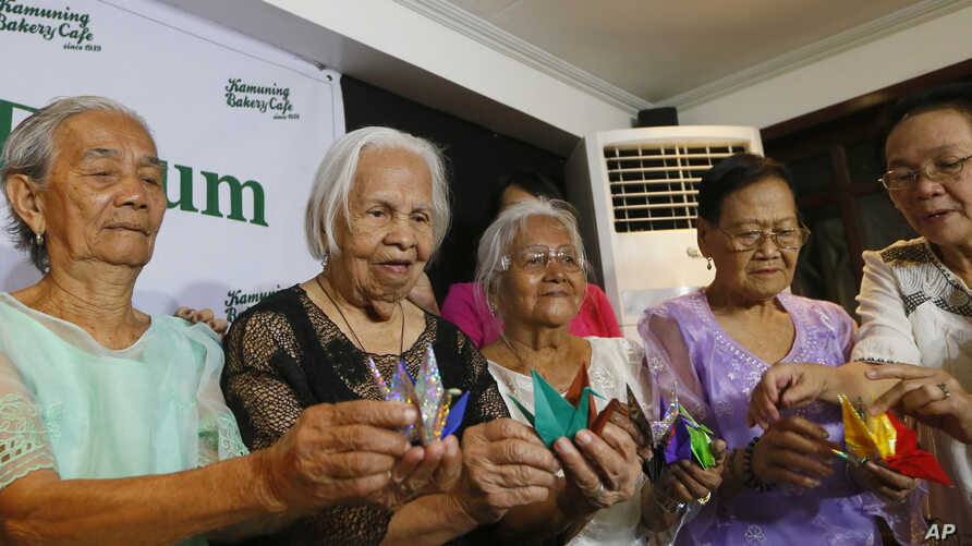 Filipino women who said they were detained and used as sex slaves by the Japanese military display Origami paper cranes to symbolize peace during a forum to demand justice, compensation and an apology from Japan, in Quezon city, Philippines, Jan. 22,