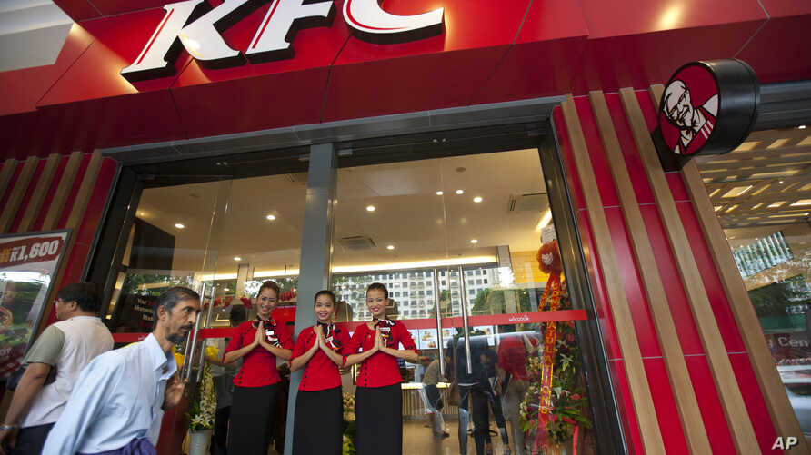 Staff members greet visitors at its grand openning, first branch of Kentucky fried chicken (KFC) restaurant, June 30, 2015, in Yangon, Myanmar.