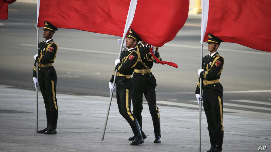 A member of a Chinese honor guard holds his red flag while losing his balance by a strong wind as he waits for the arrival of Sri Lanka's Prime Minister Ranil Wickremesinghe during a welcome ceremony outside the Great Hall of the People in Beijing, A...