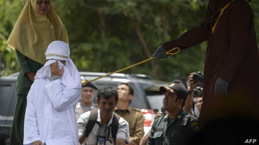 Tjia Nyuk Hwa, 45, an Indonesian Christian is publicly flogged outside a mosque in Banda Aceh on February 27, 2018, for playing a children's entertainment game seen as violating Islamic law.