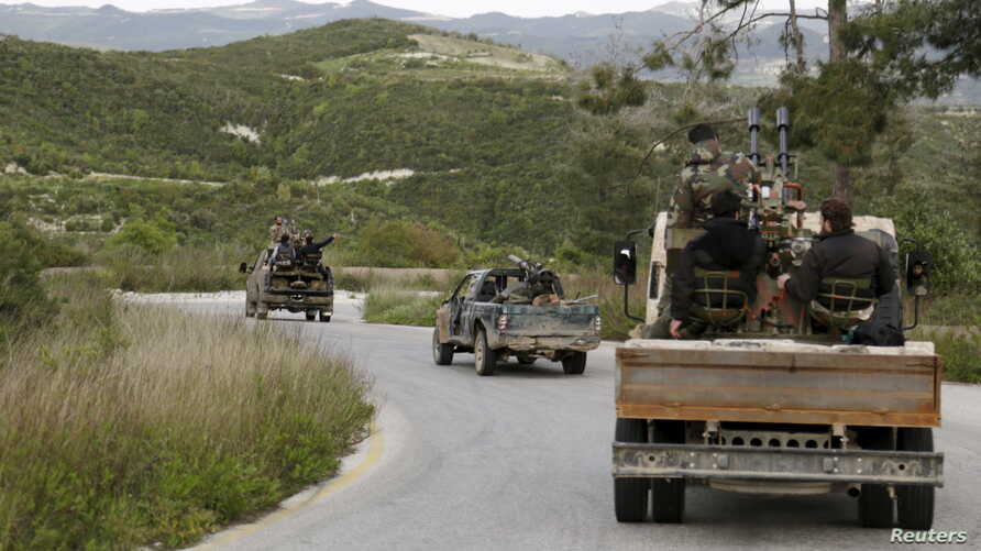 Rebel fighters drive in a convoy as they head towards what they said was an offensive to take control of Jisr al-Shughour and the surrounding areas, which are controlled by forces loyal to President Assad, April 20, 2015.
