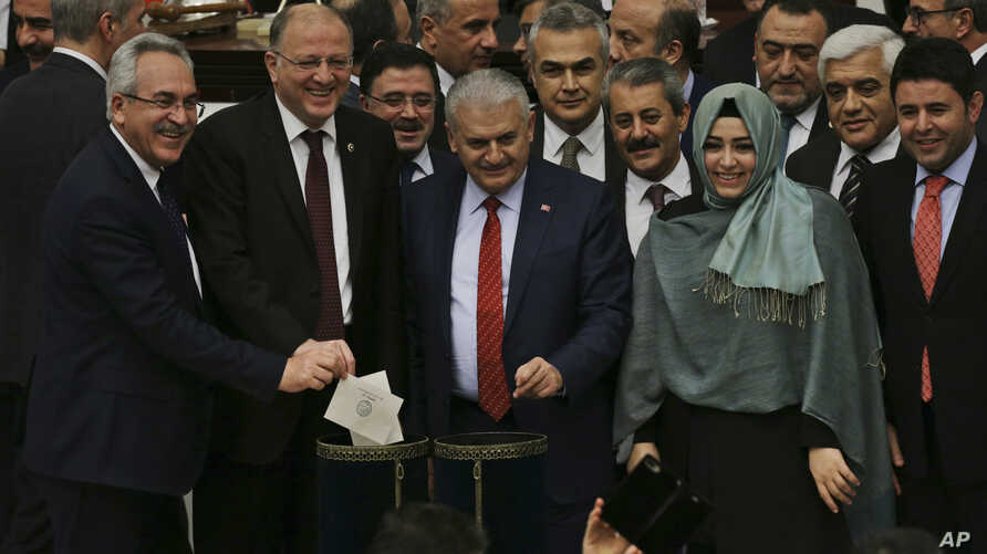 Turkish Prime Minister Binali Yildirim, center, and lawmakers cast their votes during Turkey's parliamentary debate proposing constitutional amendments that would hand President Recep Tayyip Erdogan's largely ceremonial presidency sweeping executive