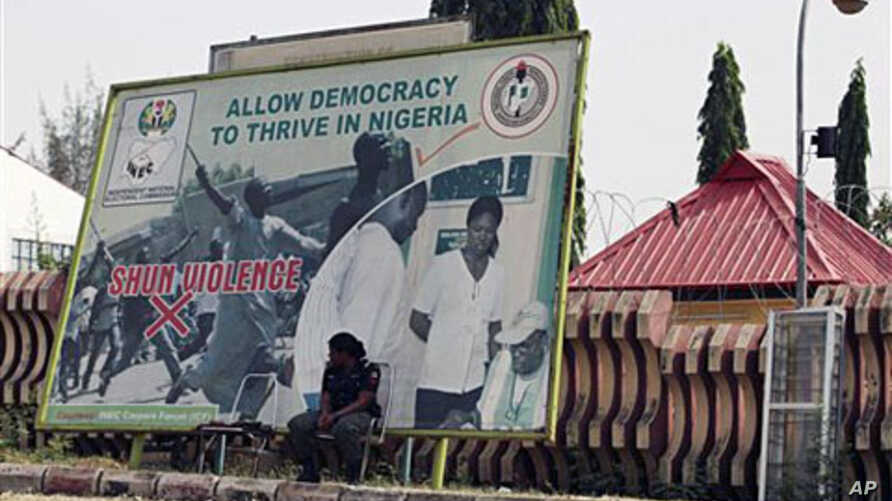 A police officer takes a break under an election billboard in front of the Independent National Electoral Commission office in Abuja, Mar 17 2011